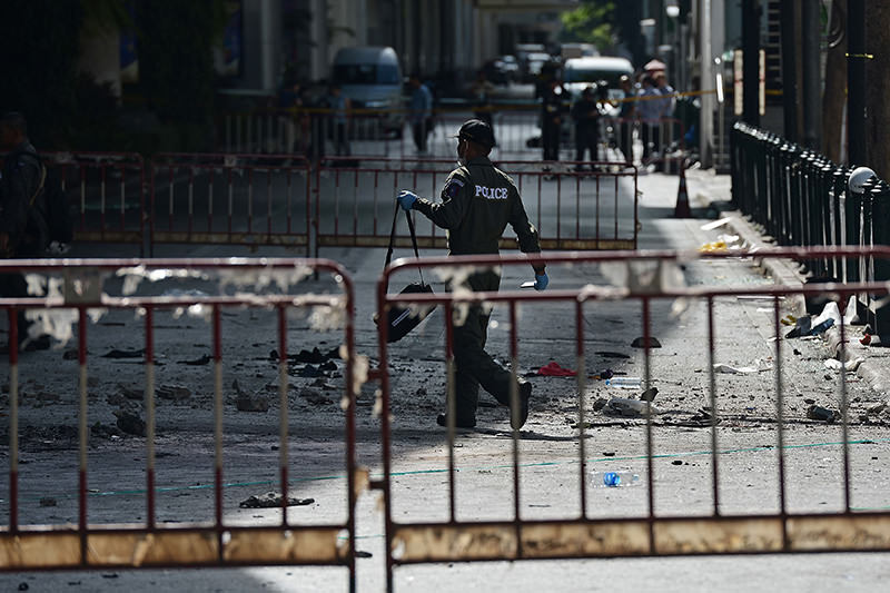 A police officer walks at the cordoned-off site of a bomb blast outside the popular Erawan shrine in the heart of Bangkok's tourist and commercial centre on August 18, 2015 (AFP photo)