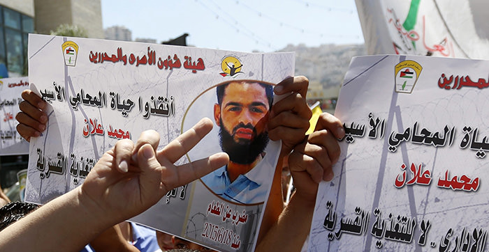 Protesters hold portraits of Palestinian prisoner Mohammad Allan, said to be held in an Israeli jail during a support rally calling for his release in the West Bank city of Nablus (EPA Photo)
