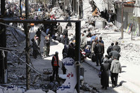 Residents wait to receive food aid distributed by the Al-Wafaa campaign at the Palestinian refugee camp of Yarmouk, south of Damascus April 1, 2014 (Reuters Photo)