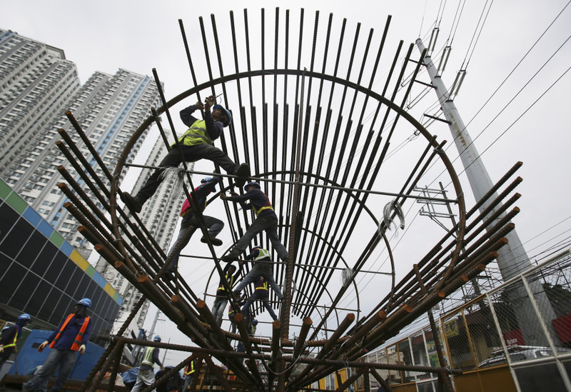Filipino workers arrange metal rods at a government road project in suburban Quezon City, north of Manila, Philippines.
