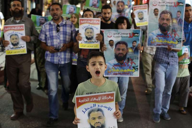Palestinian protesters rally for Mohammed Allan (portraits), who's life is at risk after hunger strike against detention without trial. (AFP Photo)