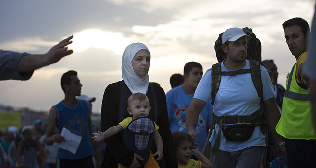 Migrants and refugees walk to board an Athens-bound ferry at the southeastern island of Kos, Greece, Friday, Aug. 14, 2015 (AP photo)