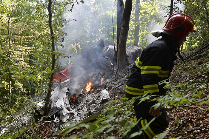 A firefighter inspects the crash site of two sport planes near the village of Cerveny Kamen, Slovakia, August 20, 2015 (Reuters Photo)