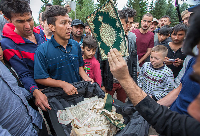 A torn Koran is presented as some refugees exclaim the expression 'Allah is great' in front of the refugee accomodation in Suhl, Germany, 20 August 2015 (EPA Photo)