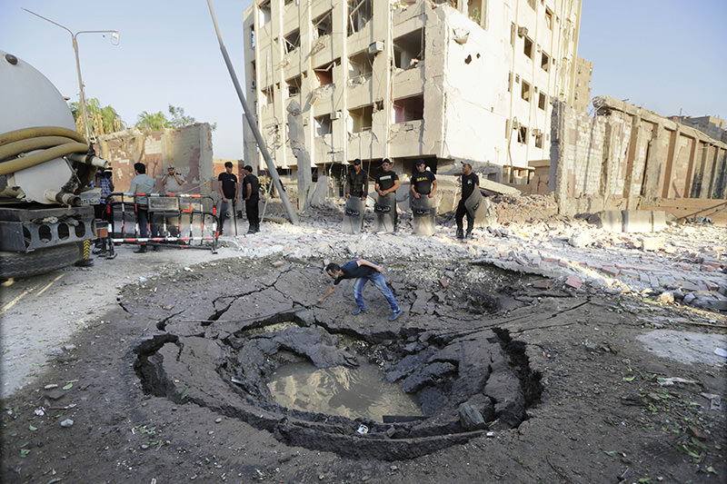 An Egyptian worker checks a hole believed to be caused by the bombing in the street outside the national security building early Thursday, Aug. 20, 2015, in the Shubra el-Kheima neighborhood of Cairo (AP photo)