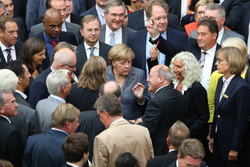 German Chancellor Angela Merkel talks to Gregor Gysi of the Left party (R) as she and members of the lower house of parliament cast their votes on Greece's third bailout program in Berlin.