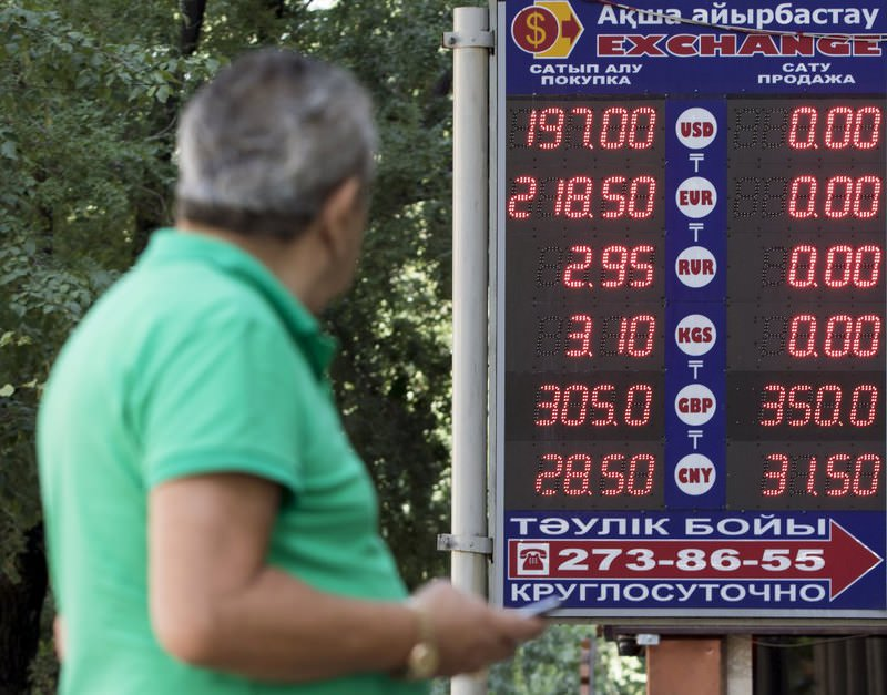 A man uses his mobile phone as he walks past a board showing currency exchange rates in Almaty, Kazakhstan.