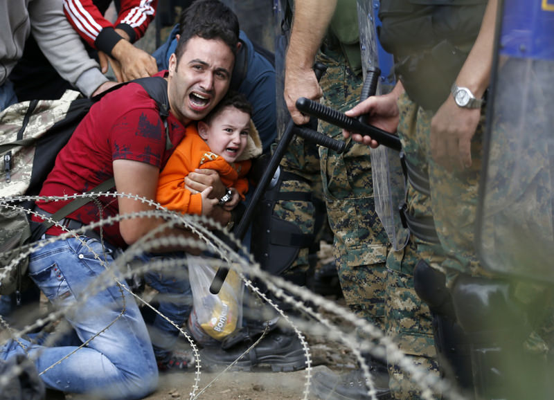 A migrant holding a boy reacts as they are stuck between Macedonian riot police and other migrants during a clash near the Greek-Macedonian border.