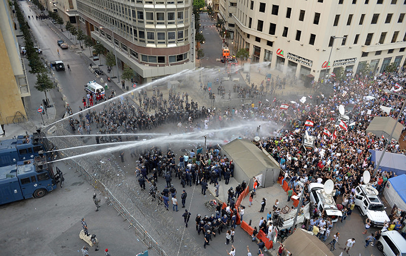 Lebanese police use water cannons to disperse activists trying to remove barbed wire blocking the entrance to the Lebanese Government Palace during a protest against the ongoing garbage crisis, downtown Beirut (EPA Photo)
