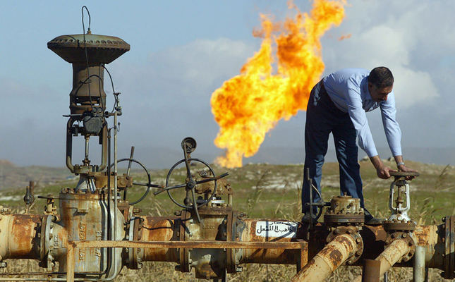A worker turns a valve at the Shirawa oilfield, where oil was first pumped in Iraq in 1927, outside the northern city of Kirkuk 19 January 2004 (AFP Photo).