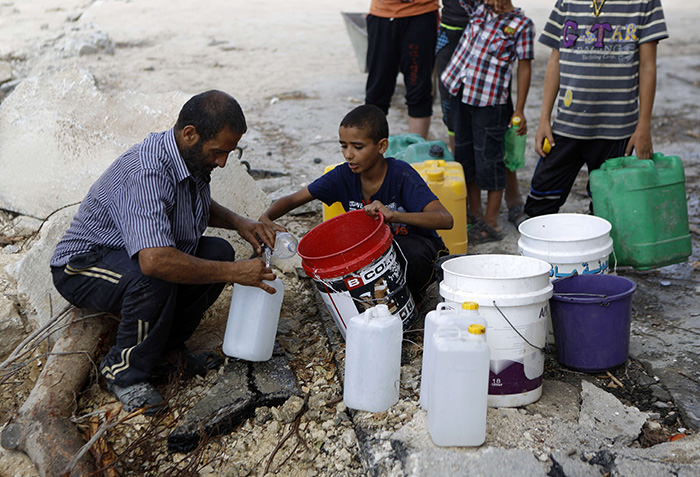 A Palestinian man and children fill containers with water from a broken main in Gaza City's al-Shejaea neighborhood on August 6, 2014 (AFP Photo)