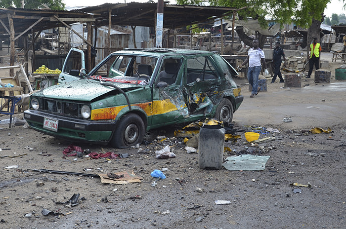 People walk past a damaged car at the site of a bomb explosion in Maiduguri, Nigeria, Friday, July 31, 2015 (AP Photo)