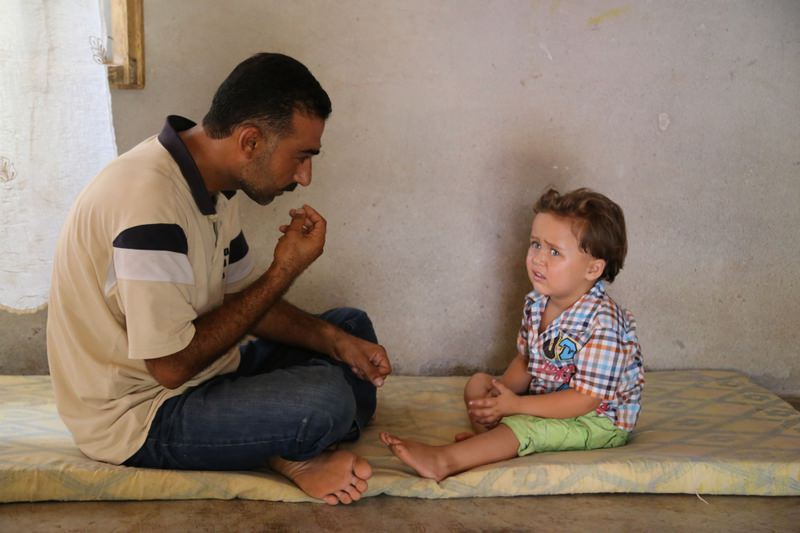 Yusuf with his hearing-impaired nephew Adnan Vail. The young boy living in an underfurnished house with his uncle's family hopes to hear again with a new hearing aid.