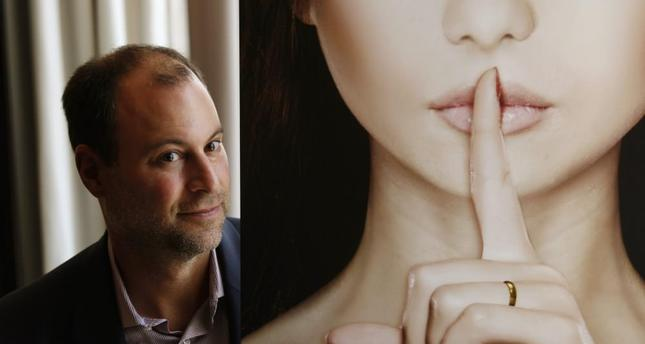 Ashley Madison founder Noel Biderman poses with a poster during an interview at a hotel in Hong Kong.