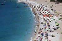 Holidaymakers enjoy the sea and fine weather in an aerial view of a Southern Aegean coast.