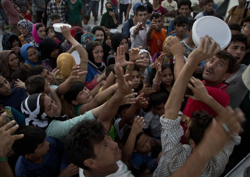 Afghan migrants push to reach for food rations at the Moria refugee camp near the town of Mytilene on the southeastern Greek island of Lesbos.