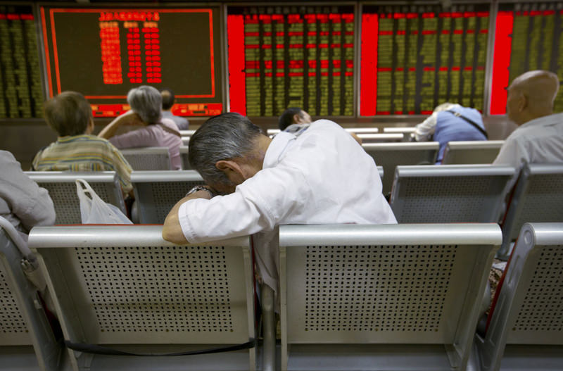 Chinese investors monitor stock prices at a brokerage house in Beijing, yesterday. China's main stockmarket index has fallen for a fourth day, plunging 7.6 percent to an eight-month low.