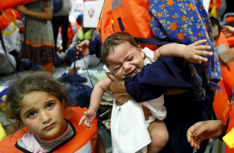 Migrant children on the Migrant Offshore Aid Station (MOAS) ship MV Phoenix wait to be transferred to the Norwegian ship Siem Pilot off the coast of Libya August 6, 2015. (REUTERS Photo)