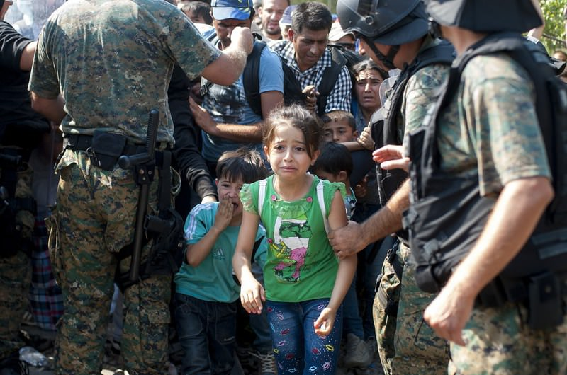 Migrants move past Macedonian police while attempting to enter Macedonia at the Greek-Macedonian border near the town of Gevgelija