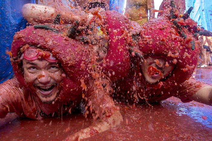 Revellers slide around in tomato pulp during the annual ,tomatina, festivities in the village of Bunol, near Valencia on August 26, 2015 (AFP Photo)