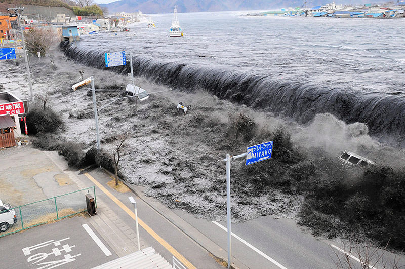 A file picture dated 11 March 2011 shows waves overwhelming a levee, swallowing a seaside village near the mouth of the Hei River, in Miyako city, Iwate prefecture, Japan (EPA photo).