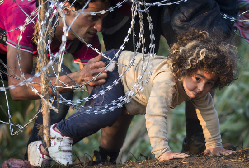 A refugee girl crawles under razor wire as she crosses from Serbia to Roszke, Hungary.