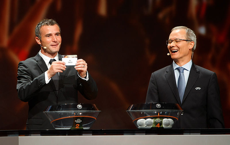 Former Swiss player Alexander Frei, left, shows the draw AZ, as UEFA Director of competitions Giorgio Marchetti smiles at the Grimaldi Forum, in Monaco, Aug. 28, 2015. (AP Photo)