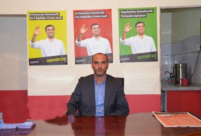 HDP's Eleu015fkirt branch head Engin Dursun poses in front of HDP leader Demirtau015f's posters. He was arrested on charges of aiding and abating a terrorist organization as he attempted to recruit two men for the PKK.