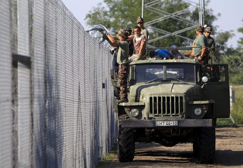 Hungarian soldiers adjust razor wire on a fence near the town of Asotthalom, Hungary.