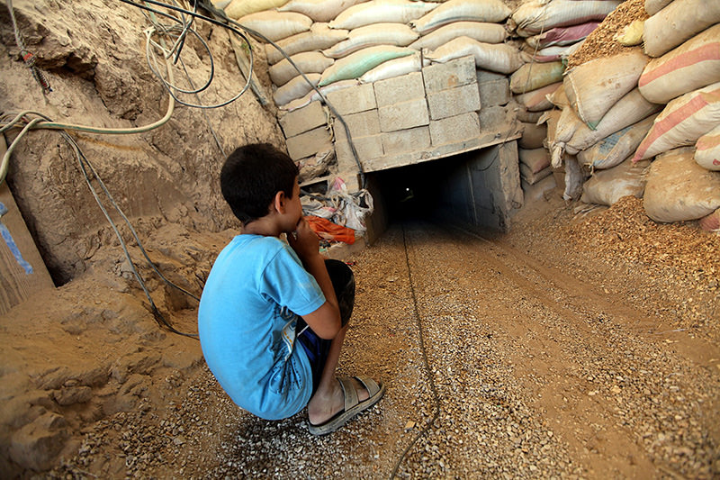 9-year-old Mohammed sits in front of a tunnel used between Gaza Strip and Egypt at Rafah border in the southern Gaza Strip, 26 August 2012. (EPA photo)