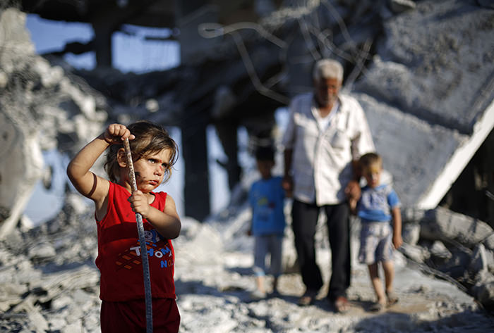 A Palestinian girl plays in the rubble of buildings destroyed during the Israeli airstrikes on Gaza in the summer of 2014 (AFP Photo)