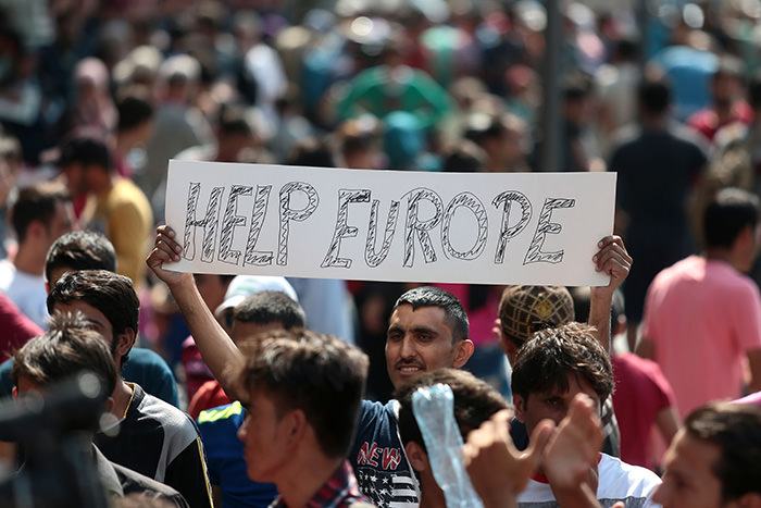 Man holds a placard reading ,Help Europe, as Syrian and Afghan refugees attend a protest to demand to travel to Germany on September 2, 2015 in Budapest (AFP Photo)