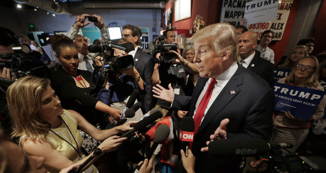 Republican presidential candidate Donald Trump answers questions from reporters after speaking at the National Federation of Republican Assemblies.