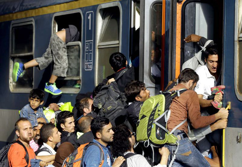 Migrants board a local train heading to the Hungarian-Austrian border at the main train station in Budapest.