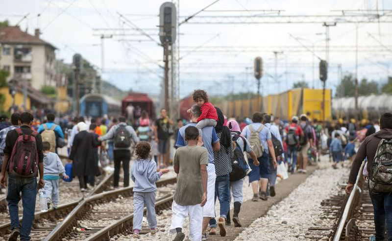 Migrants walk on train tracks towards the town of Gevgelija after breaking through a cordon of Macedonian special police forces.