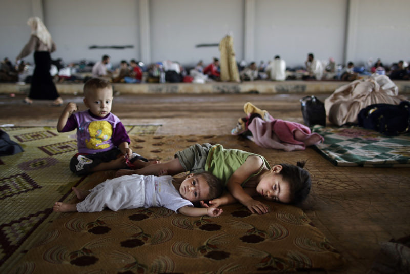 Syrian children who fled their homes with their families due to the Syrian civil war lie on the ground in hopes of entering one of the refugee camps in Turkey.