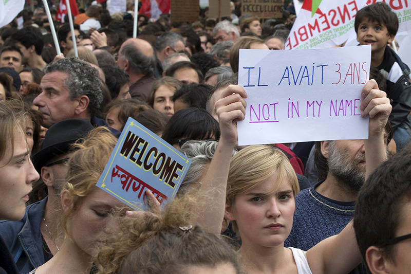 A woman holds a sign that says ,He was three; Not in my name, as she attends a demonstration in France (Reuters Photo)