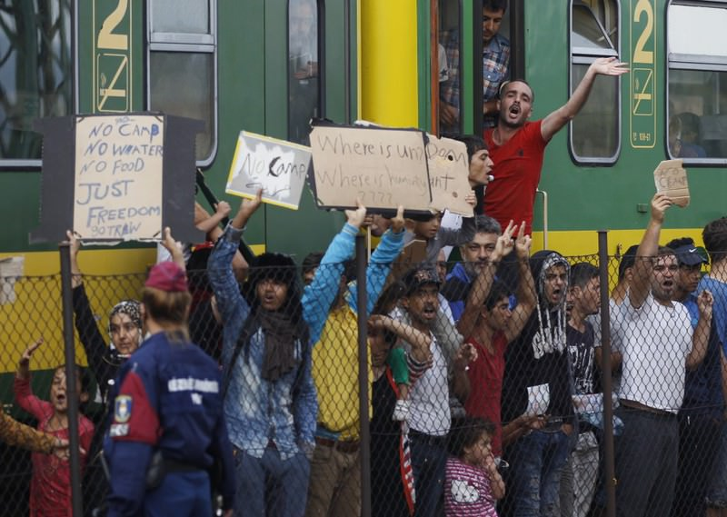 People shout slogans outside a train that was stopped in Bicske, Hungary.