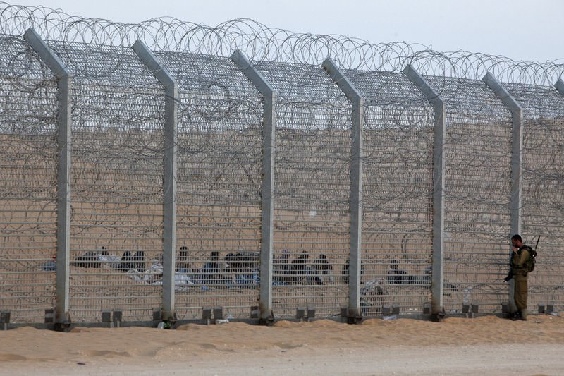 An Israeli soldier stands near the border fence between Israel and Egypt as African migrants sit on the other side near the Israeli village of Be'er Milcha, in this September 6, 2012 file photo. (REUTERS Photo)