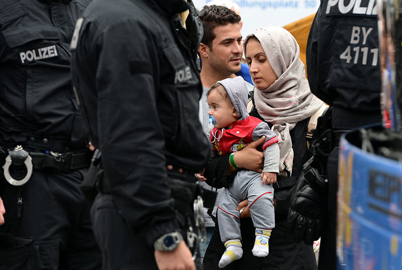 Refugee woman with child waits for a bus after their arrival at the main train station in Munich, southern Germany, on September 05, 2015 (AFP Photo)