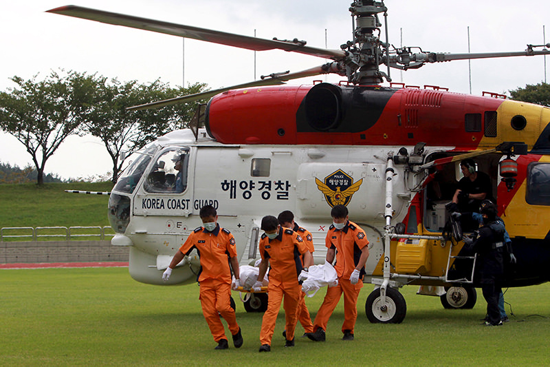 South Korean Coast Guard personnel carry the body of a passenger who was onboard a boat called Dolgorae, or Dolphin, which capsized at the sea off the southern island of Jeju in Heanam  (Reuters Photo)