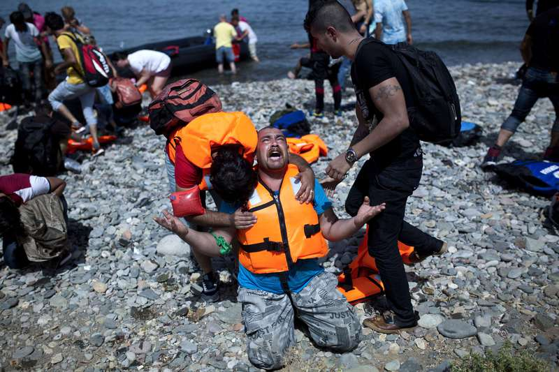 A Syrian refugee prays after arriving on the shores of the Greek island of Lesbos aboard an inflatable dinghy across the Aegean Sea from from Turkey on September 7, 2015. (AFP Photo)
