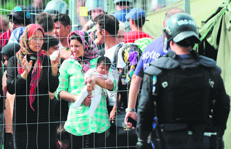 Hundreds of migrants wait behind a fence in Hungary with no access to water, food or other basic needs.