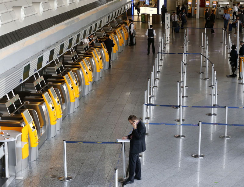 A passenger makes a phone call near empty Lufthansa counters when Lufthansa pilots went on a six-hour warning strike at the Frankfurt airport on Sept.5. The German Pilots' Association announced a one-day strike starting today.