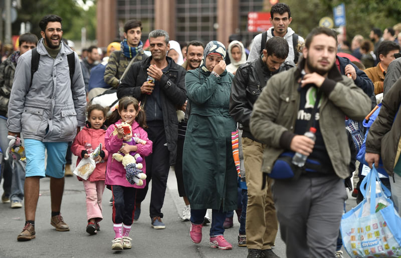 Migrants walk from the main station in Dortmund, Germany, to a hall where they get first attendance.