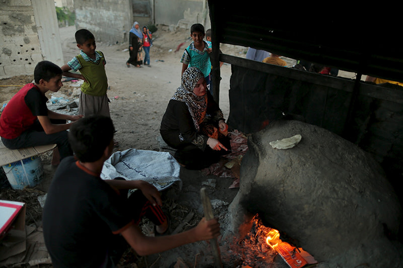 Palestinians bake bread on a clay oven in Beit Lahiya town in the northern Gaza Strip August 25, 2015 (Reuters Photo)