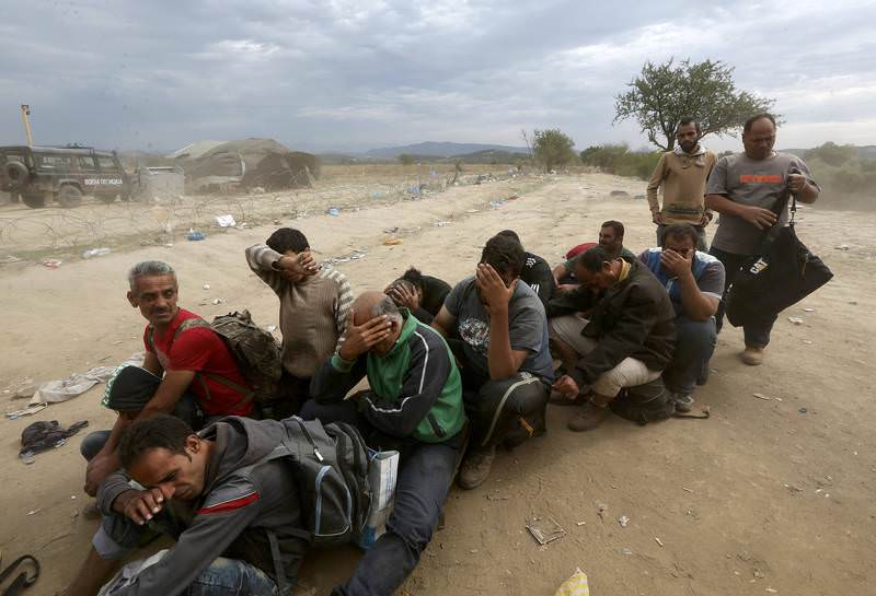Syrian refugees try to protect themselves from gusts of wind and dust as they wait to cross Greece's border with Macedonia September 7, 2015. (REUTERS Photo)