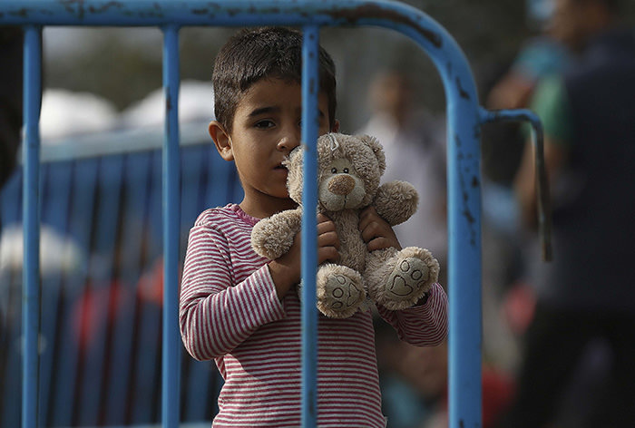 A Syrian refugee boy holds his teddy as he waits behind police barriers at Greece's border with Macedonia, near the Greek village of Idomeni, September 9, 2015 (Reuters Photo)