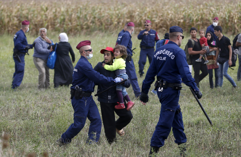 Hungarian police officers stop a group of migrants near a temporary holding center for asylum seekers on Tuesday in Roszke, southern Hungary.