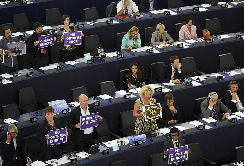 Parliament members holds posters while European Commission President Jean-Claude Juncker delivers his State of the Union address at the European Parliament in Strasbourg, eastern France (AP Photo)